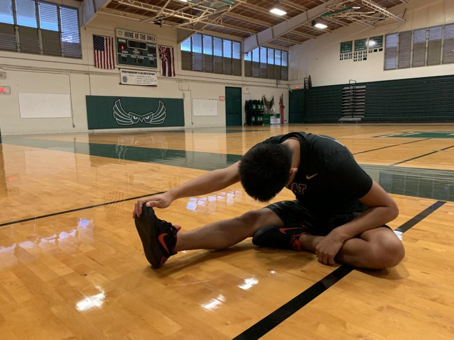 Adonis Espania stretching in preparation for the Boys varsity basketball game.