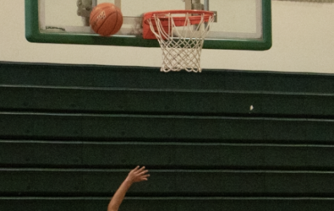 Girls varsity basketball team members Zannah Suehiro shoot the ball during practice, while Madi Sagawa rebounds. The team has improved their record since last year under a new coach.