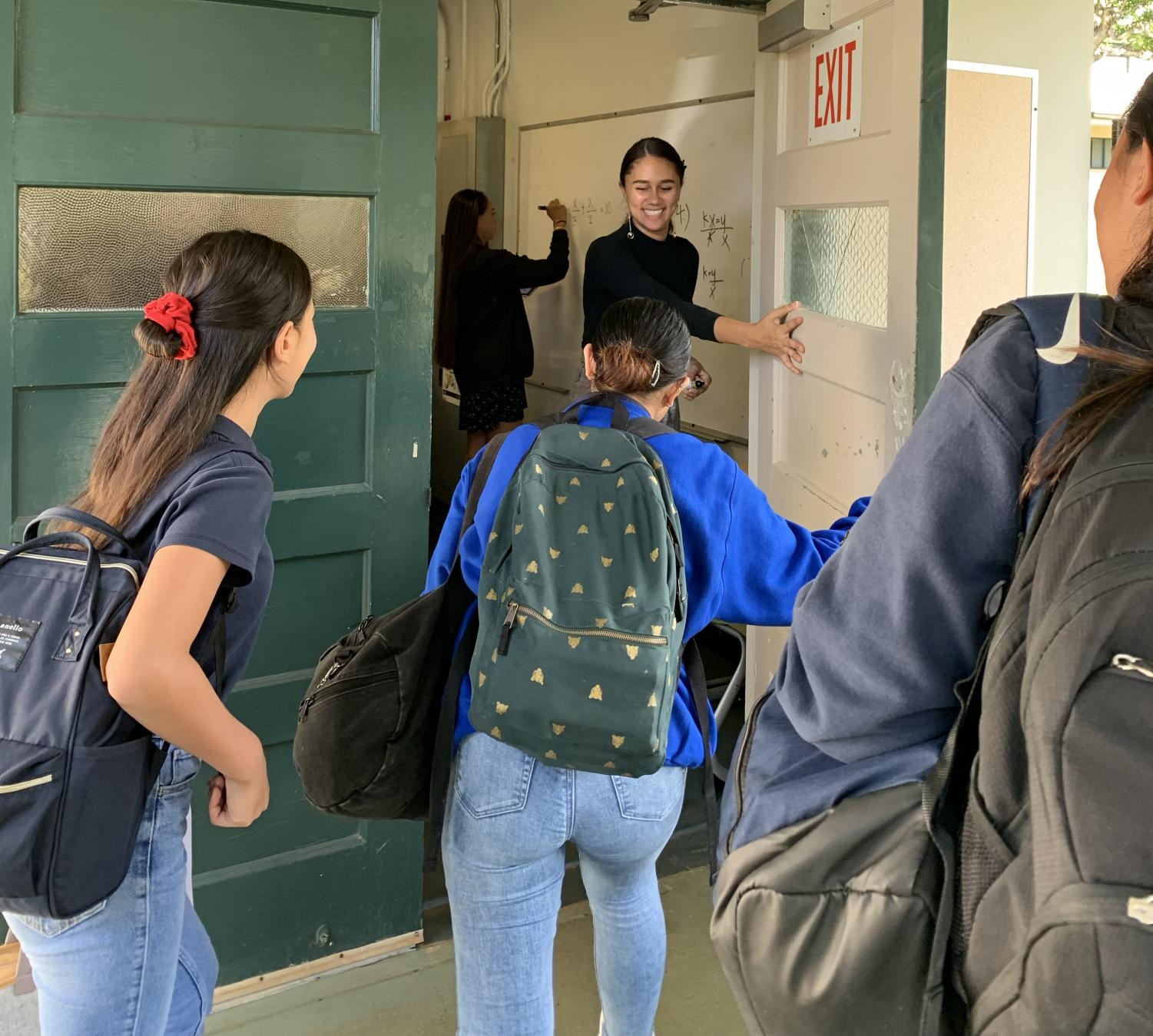 Junior Sarae Miguel opens the door and welcomes 8th graders to the Algebra 2 classroom.