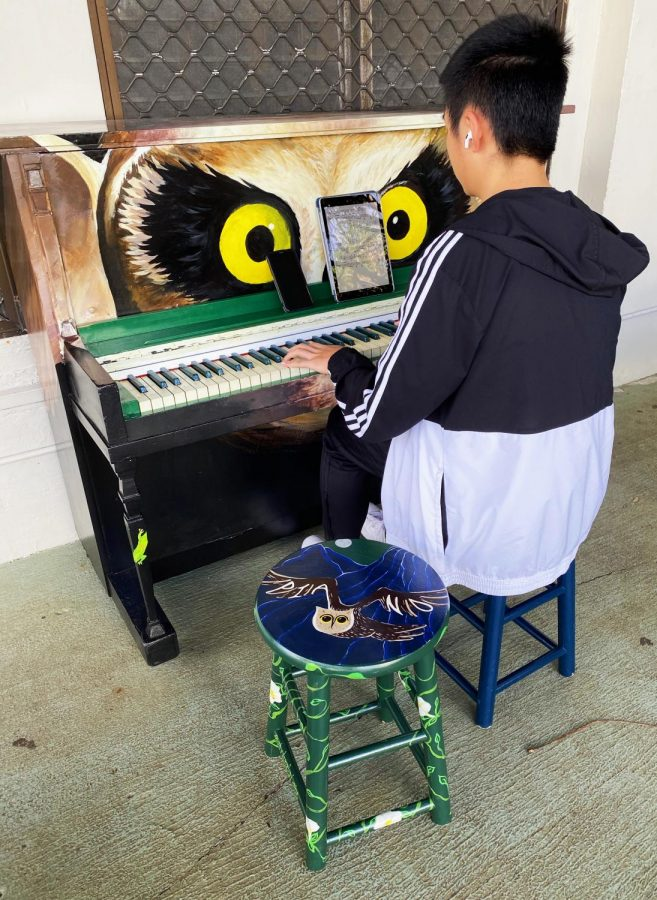 Student playing new piano outside the cafeteria.