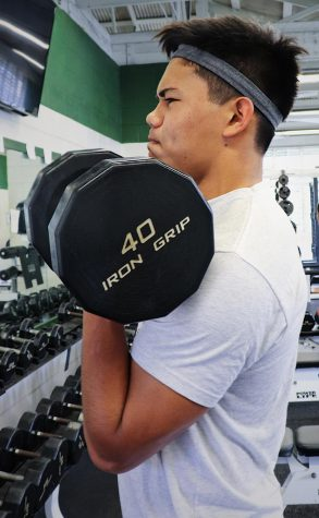 Junior Rocket Uechi practices a bicep curl at the Mid-Pacific weight room.
