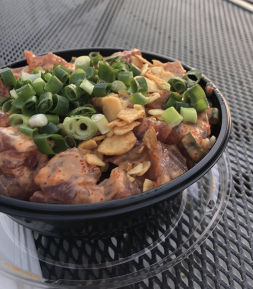 Large poke bowl with white rice, mild shoyu, furikake, spicy tuna, green onions and garlic chips about to be devoured.