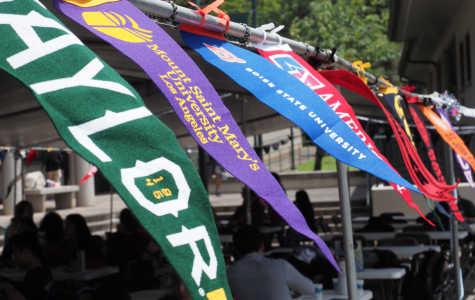 The banners of different colleges blow in the wind in unison during Mid-Pacific's 2019 college signing day. Current seniors are finding that the college application process is changing due to COVID-19.