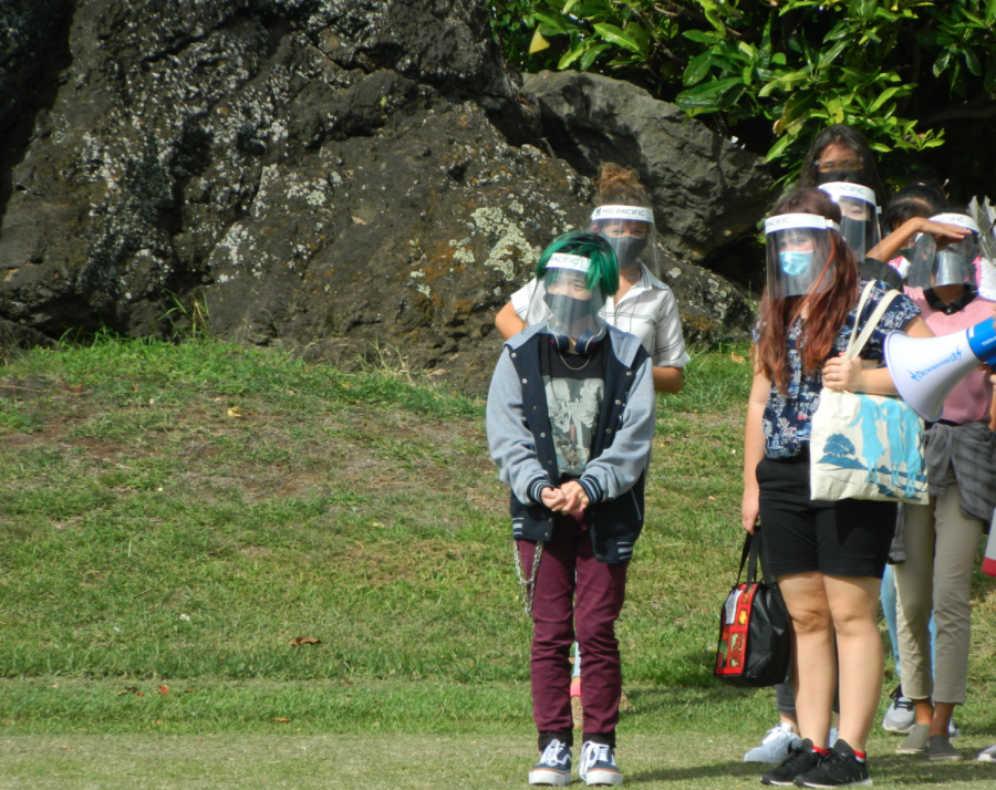Students at the freshman orientation standing with their cohorts wearing masks and face shields on the football field. Mid-Pacific brought back high school students to campus with some staying virtual for the remainder of the semester.