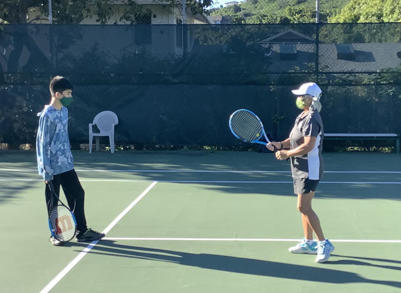 Coach Carolyn Katayama helping freshman Kekai Moriwake with swing.