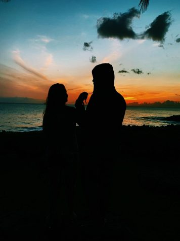Couple Kapuaanhuea Robinson and her boyfriend cuddle together as they enjoy the sunset. High school dating life has been affected by the pandemic.