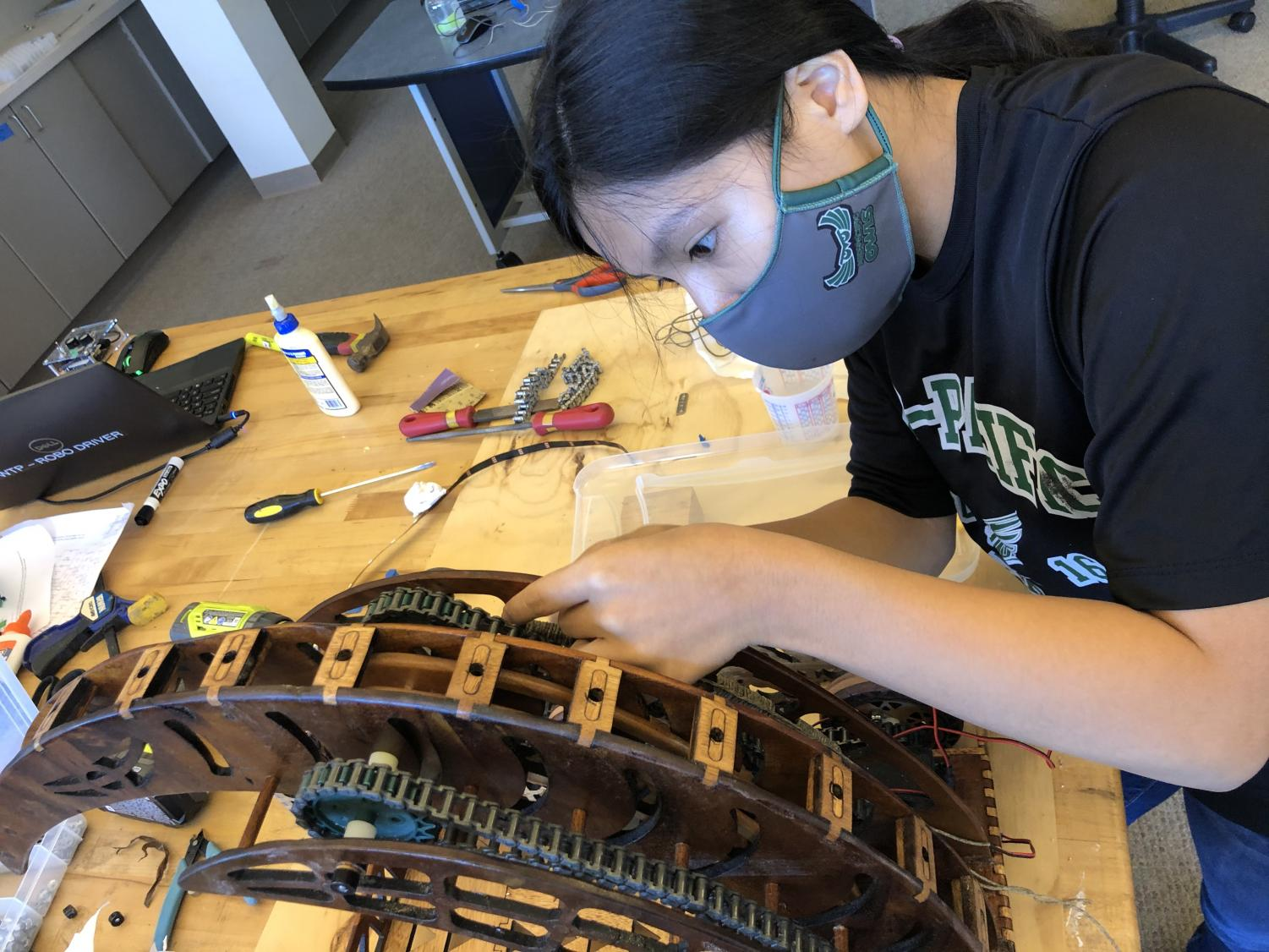 Senior Lauren Jardiolin works on attaching arch bindings to the robot. Teams had to work in groups of three to stay safe during the pandemic while building the robot.
