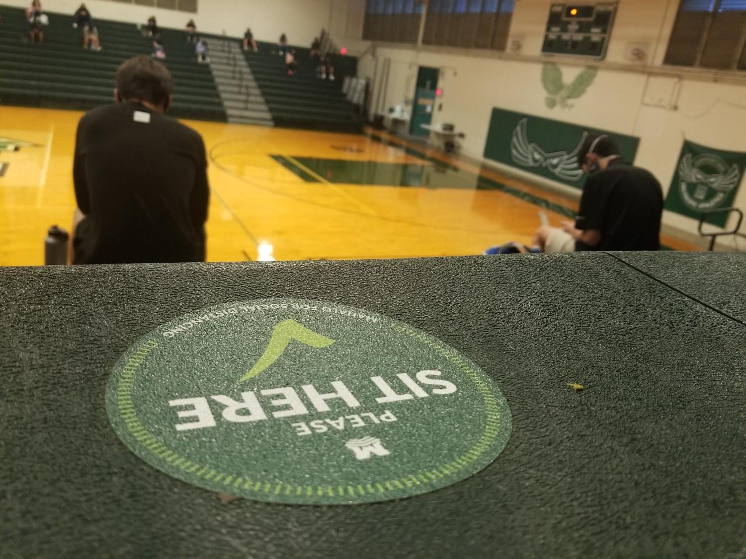 A socially distanced sticker lies in the gymnasium for students to sit and be safe. The Mid-Pacific community shared how they are coping in a CO- VID-19 school environment.