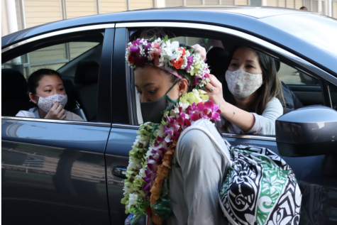 Parents adorn Zoe Oshiro with a haku lei. Parents celebrated athletes in a drive-through.
