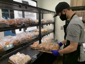 Senior Chris Wong puts down a tray of baked goods at his part time job. Students have continued to find ways to make money through a part time job or creating their own side businesses.