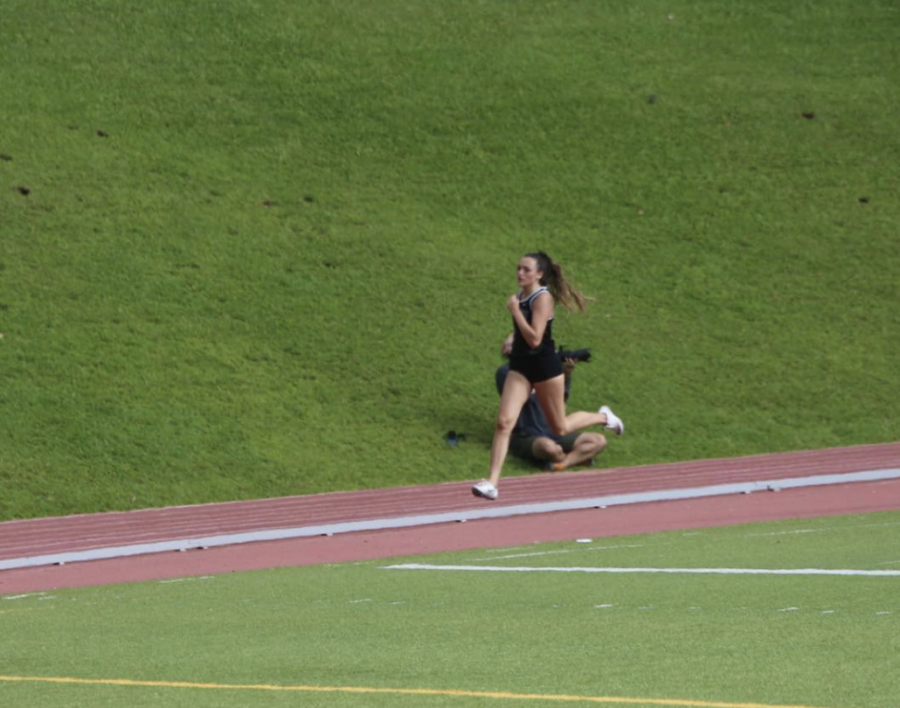 Aiming for the end of her face, now alumni, Amy Maile strides during track and field prior to covid